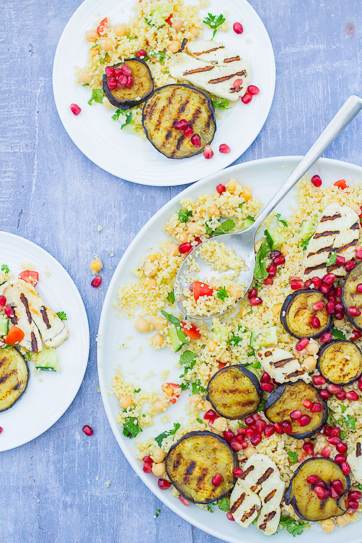 Overhead shot of Aubergine and Halloumi Salad on a serving platter and two smaller plates