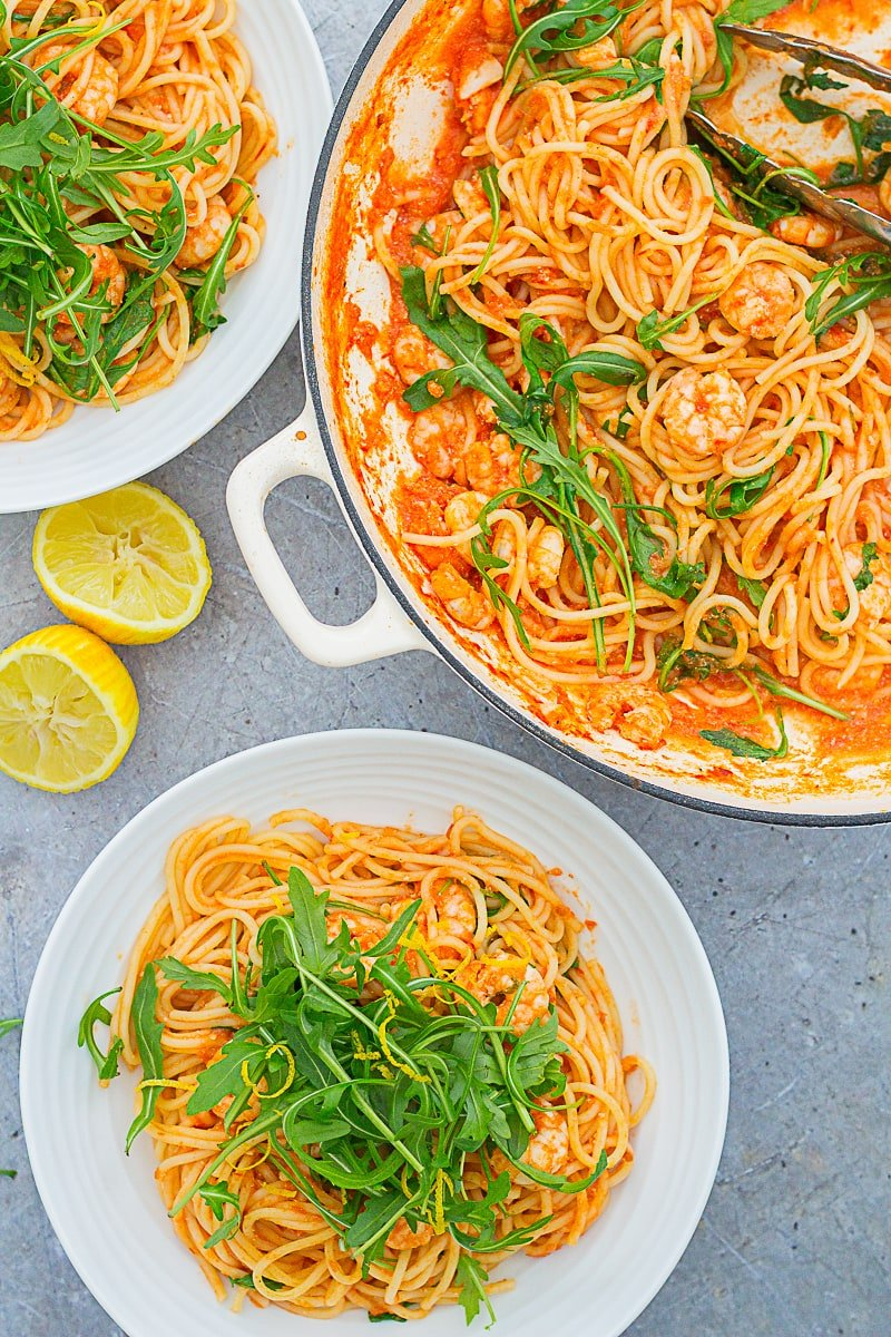 Overhead shot of two bowls and a pan filled with Easy Prawn and Rocket Spaghetti