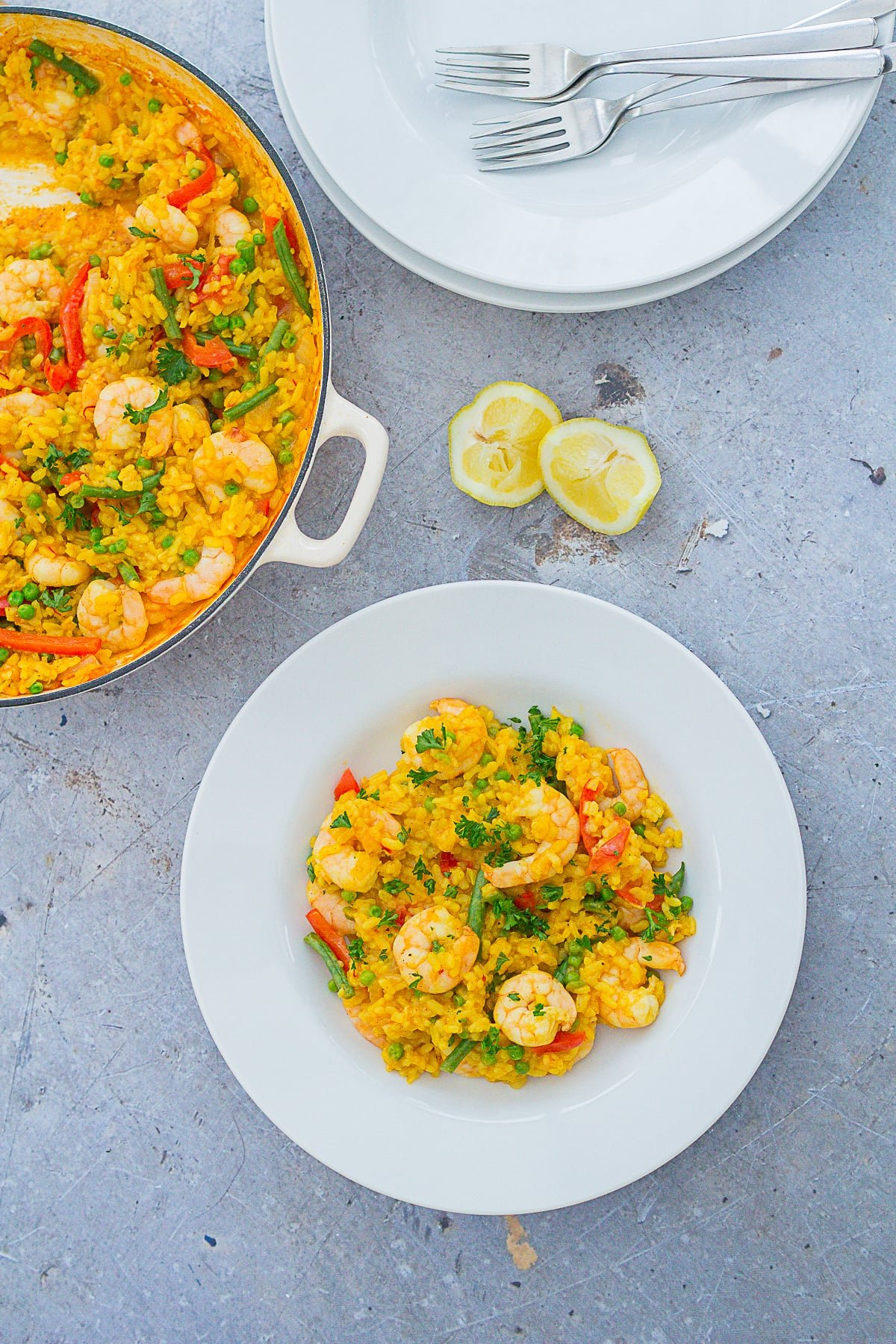 Overhead image of Easy Peasy Prawn Paella on a plate, next to a pan of paella and 2 lemon wedges