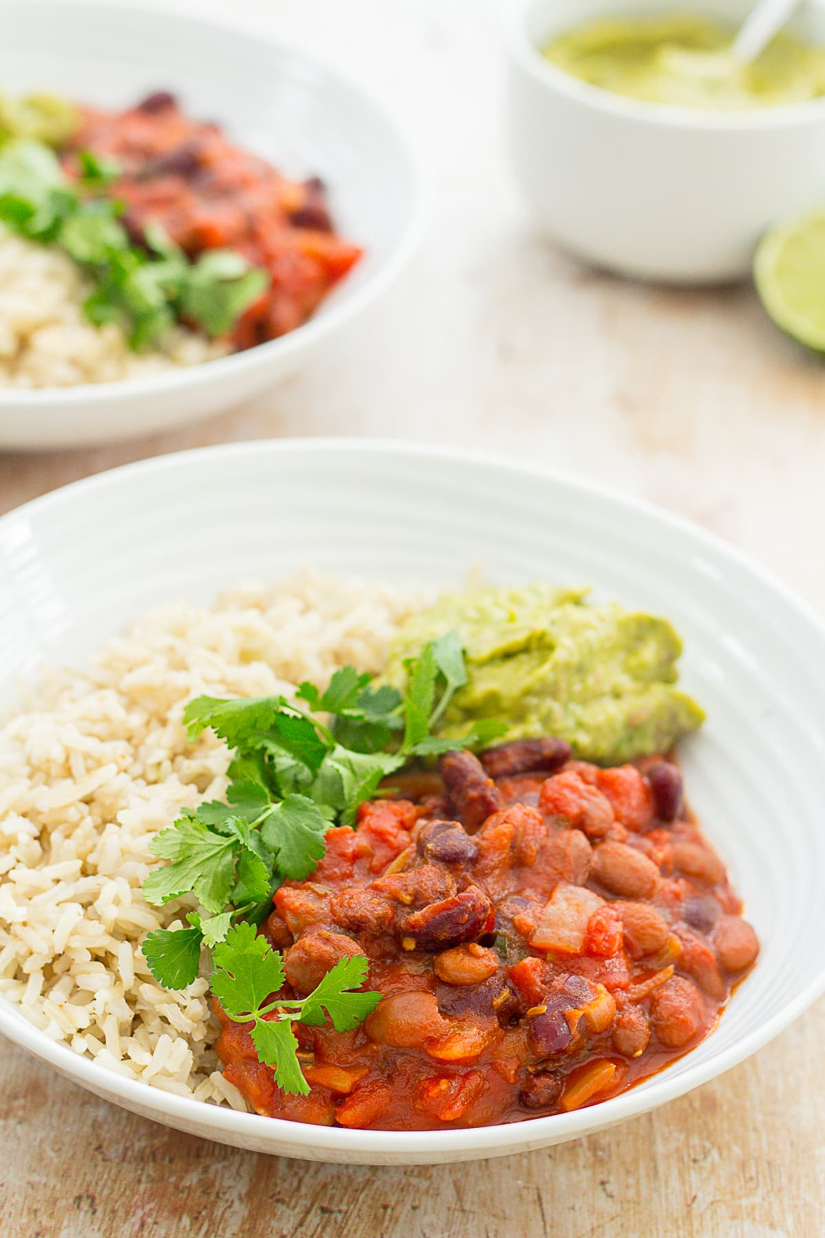 Two bowls filled with brown rice, quick beany chilli and guacamole. Garnished with fresh coriander. Next to a bowl of easy peasy guacamole and lime halves.