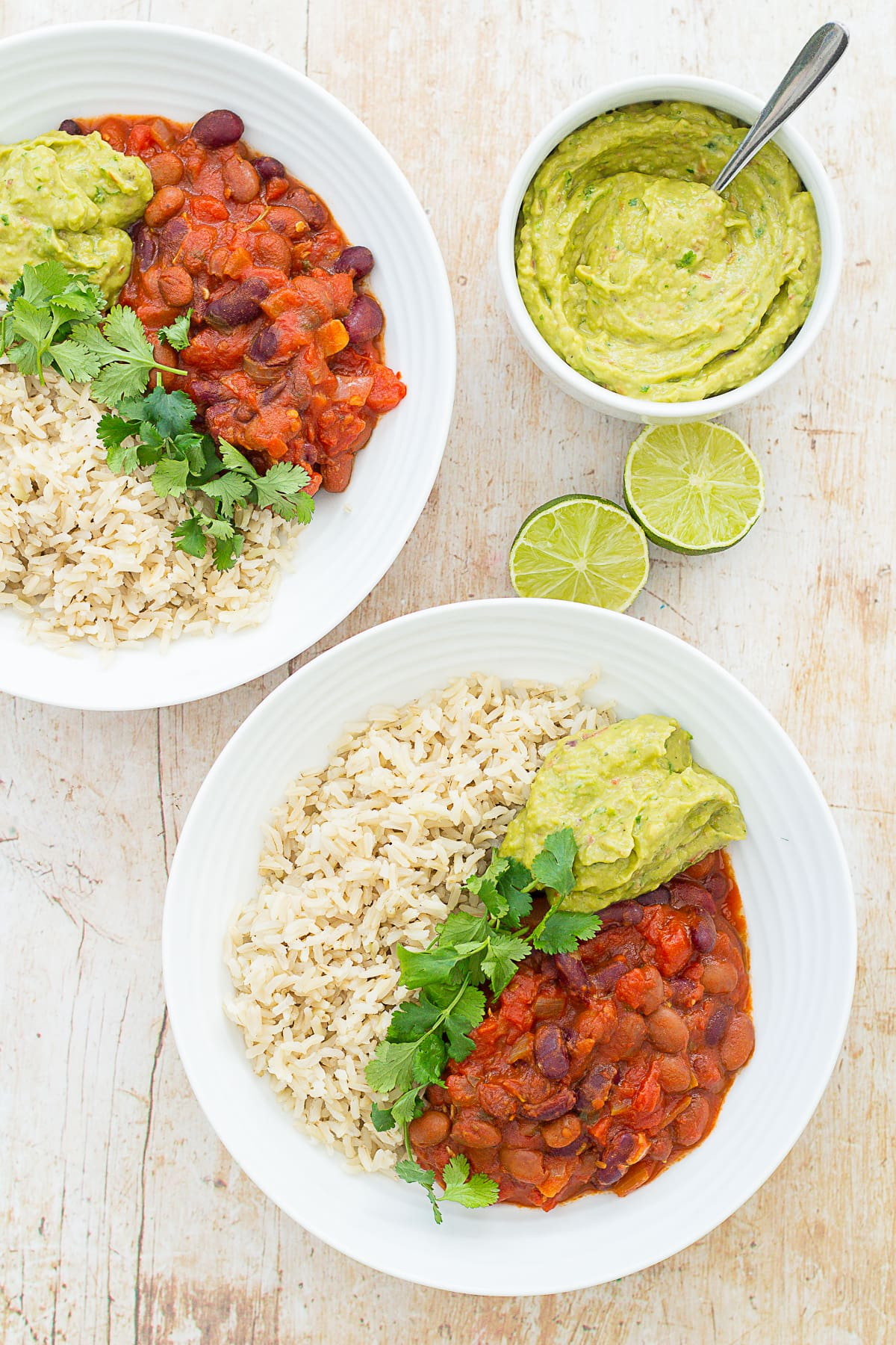 Overhead shot of two bowls filled with brown rice, quick beany chilli and guacamole. Garnished with fresh coriander. Next to a bowl of easy peasy guacamole and two lime halves.