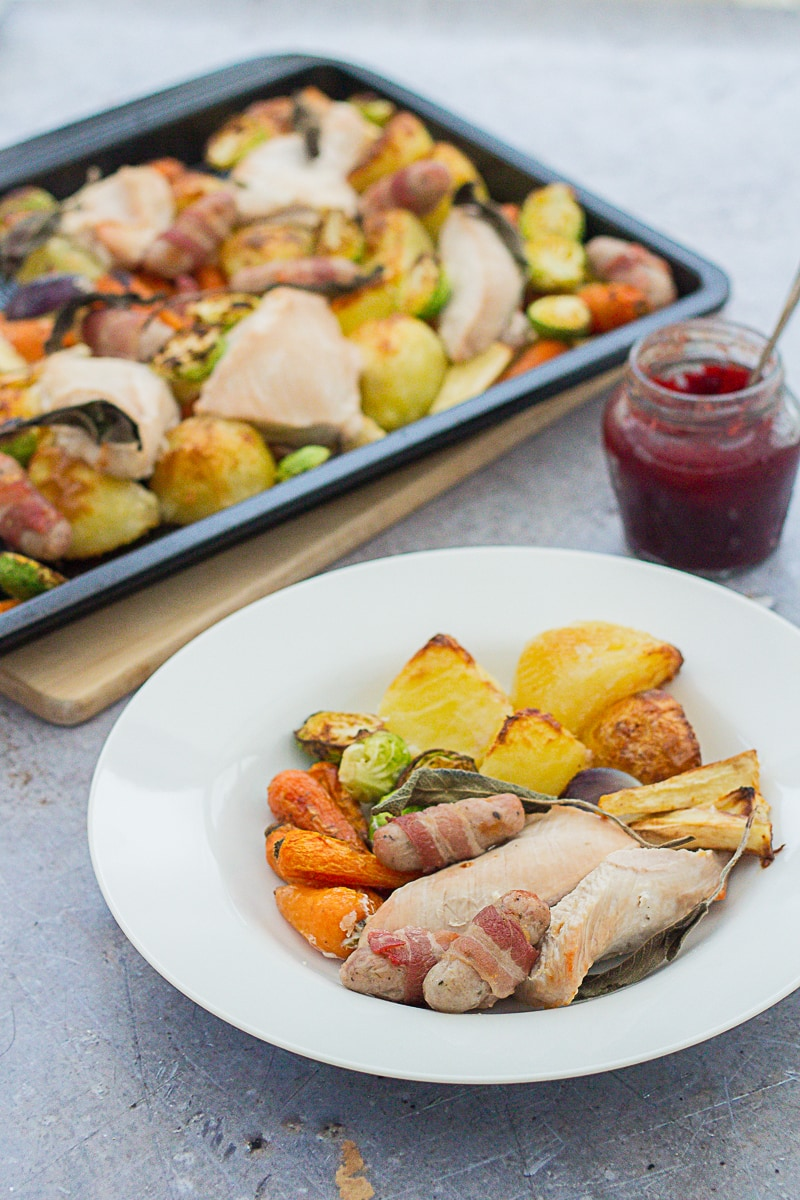 One portion of Easy Peasy Christmas Turkey Traybake on a plate with the tray behind and a pot of cranberry sauce