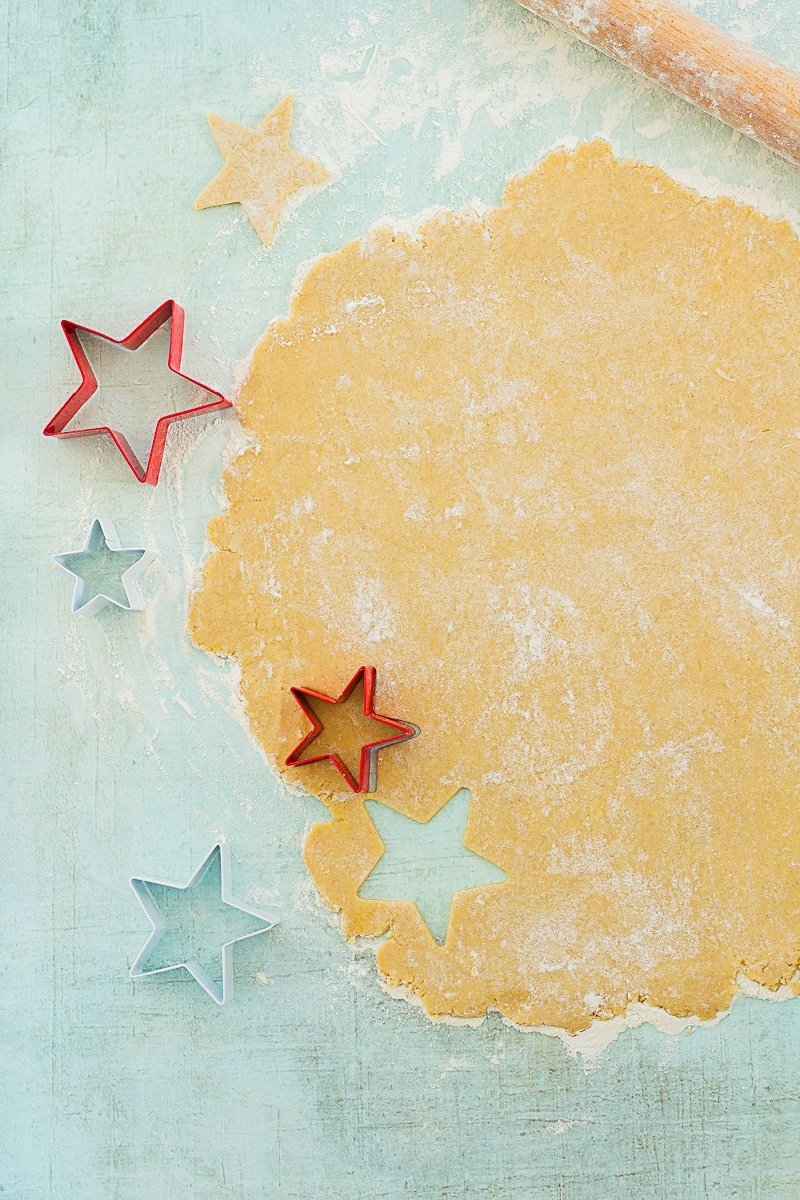 Easy Peasy Christmas Star Biscuits dough rolled out and being cut into star shapes with star cutters