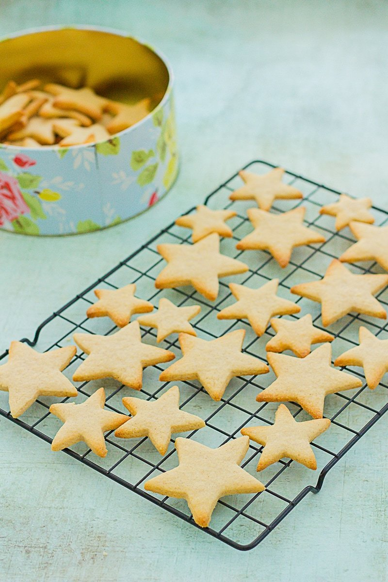 Easy Peasy Christmas Star Biscuits on a cooling wire next to a tin of the biscuits