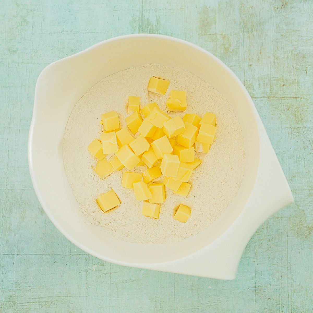 Cubes of butter on top of flour in a white bowl