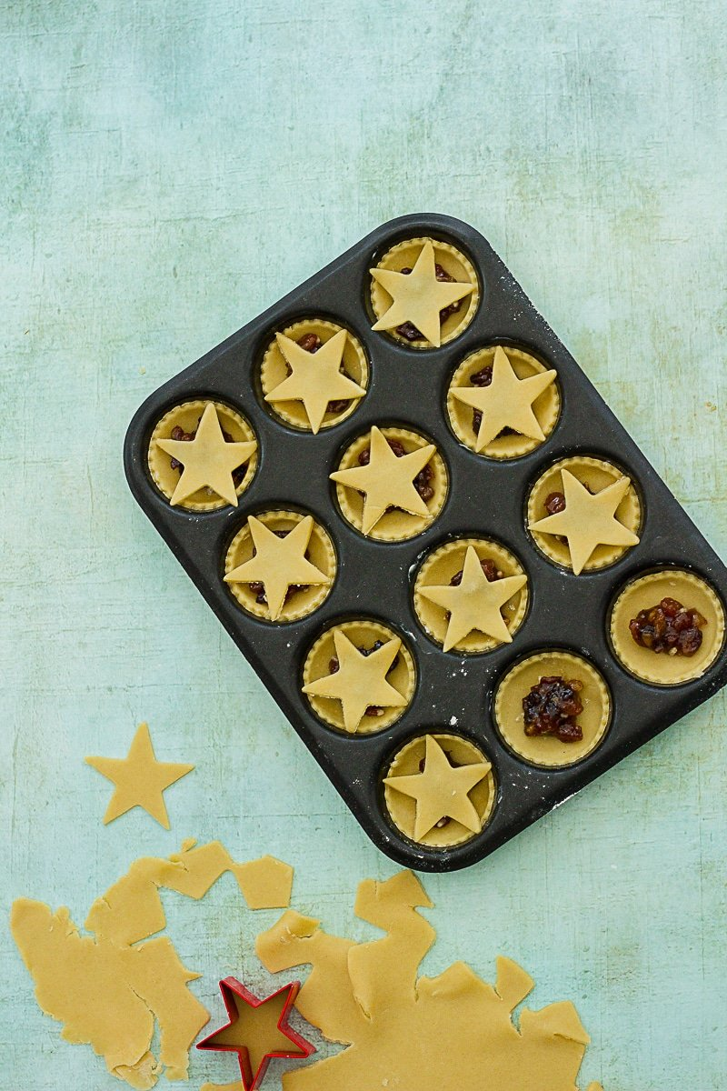 Rolled out pastry, star shaped cutter, 10 mince pies in the tin, topped with stars, 2 not yet topped.