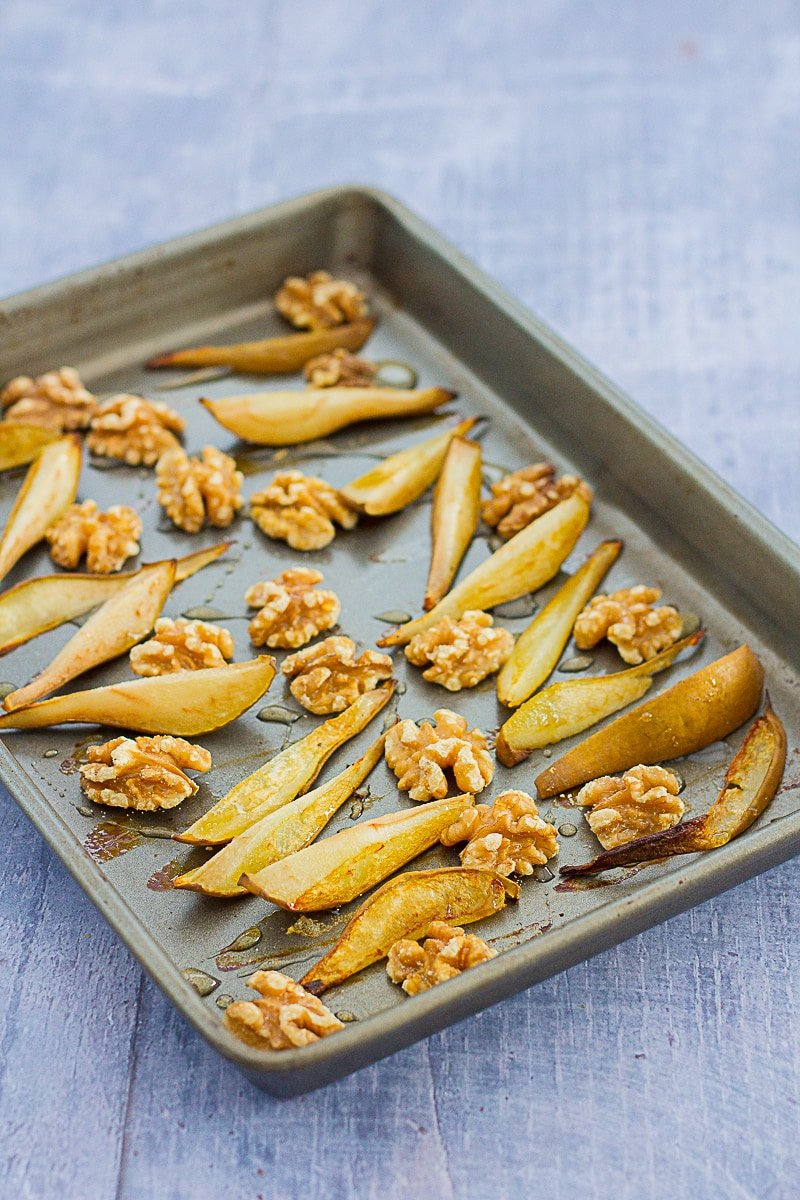 Roasted pears and walnuts drizzled with honey on a roasting tray