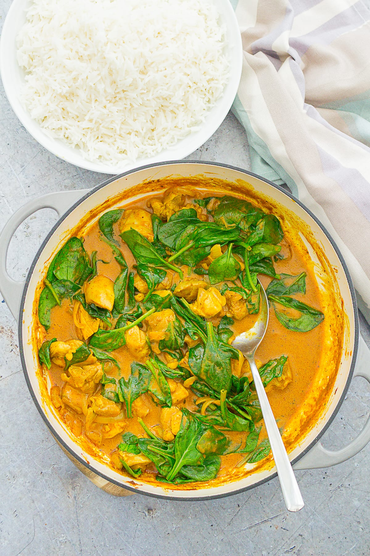 Overhead shot of Quick Chicken and Spinach Curry (Chicken Saag) in a pan next to some basmati rice