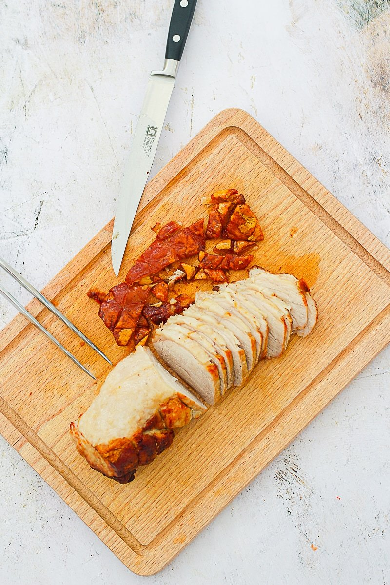 Roast pork on a chopping board, crackling removed and half sliced, plus carving knife and fork