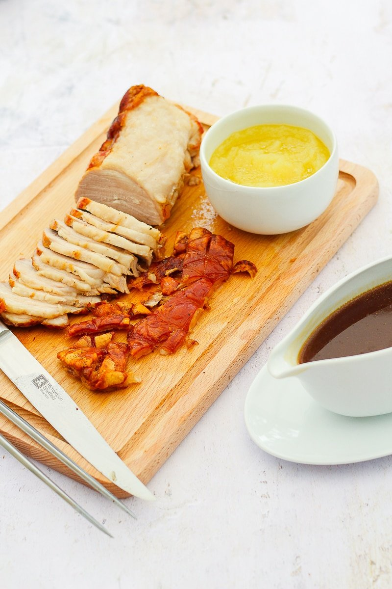 Roast pork on a chopping board, crackling removed and half sliced, plus carving knife and fork, a bowl of apple sauce and a gravy boat of pork gravy