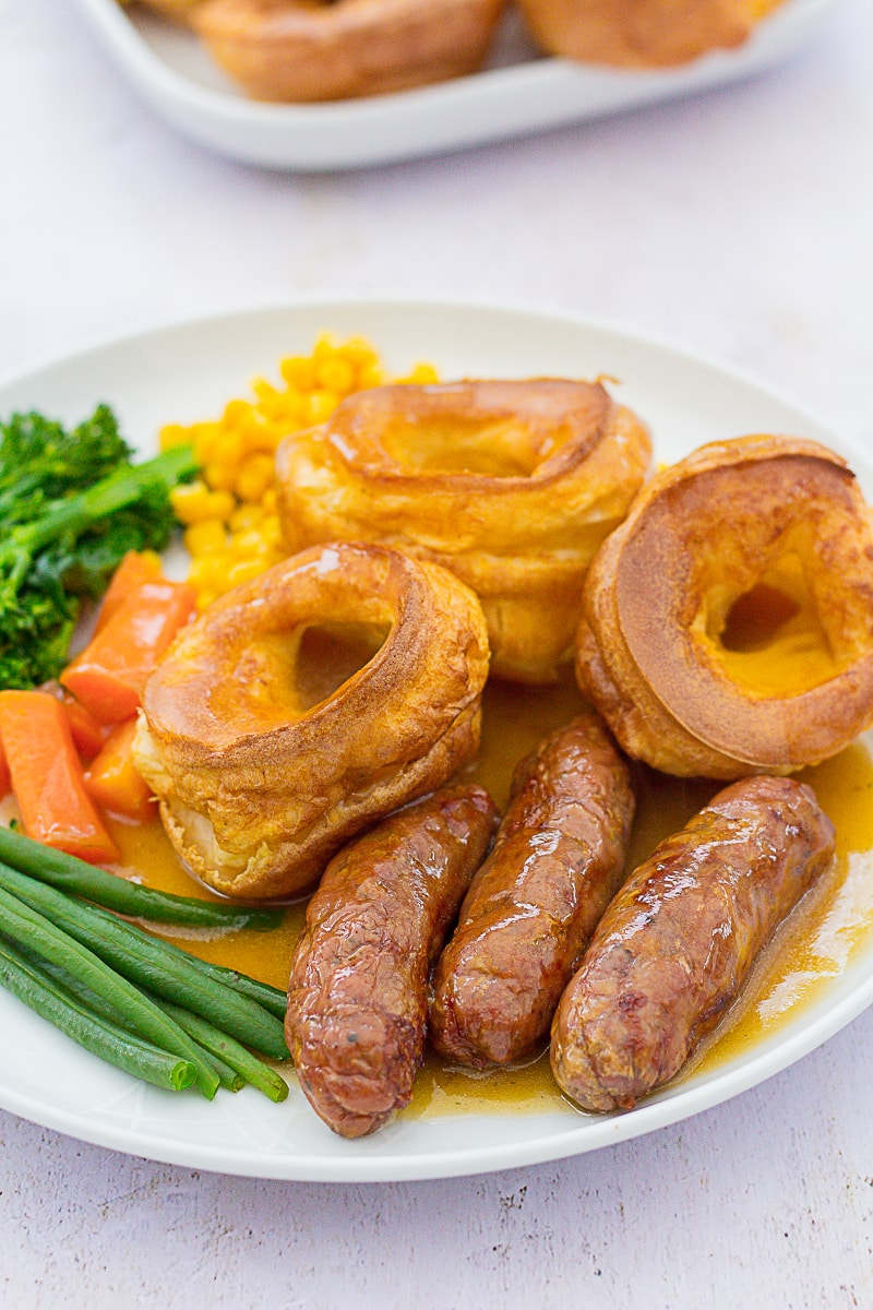 Three Yorkshire puddings on a plate with 3 sausages, plus vegetables and gravy