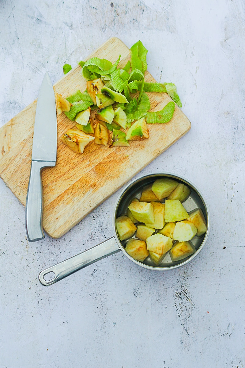 Chopped apple in a pan next to a chopping board with apple peelings and a sharp knife