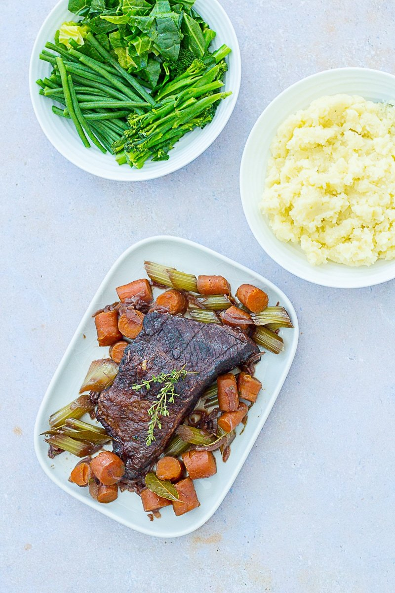 Overhead shot of Easy Peasy Pot Roast on a serving platter, with mashed potatoes and green vegetables