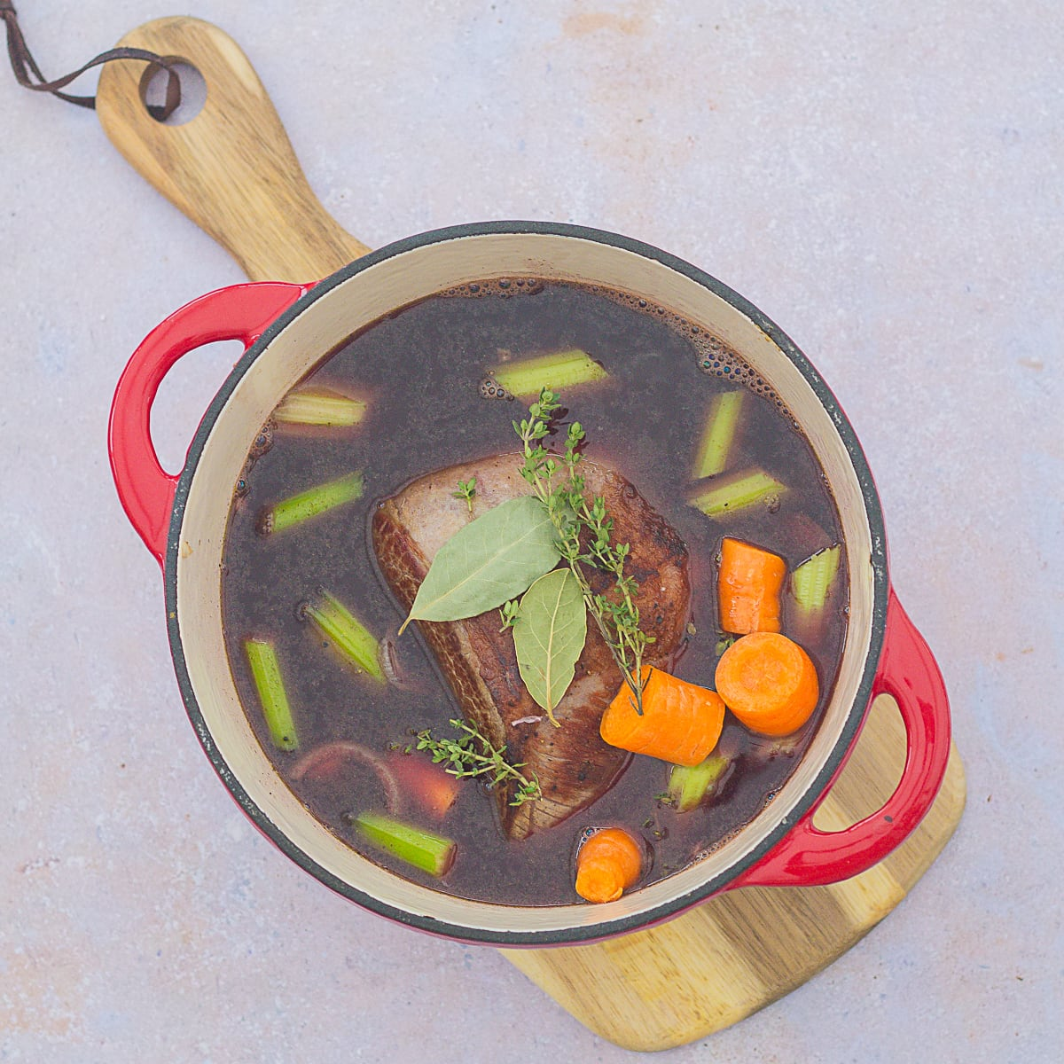 Browned beef brisket in a dutch oven with stock, red wine, carrots, celery and herbs