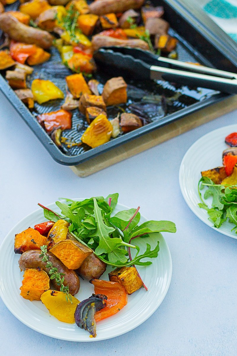 Easy Sausage and Sweet Potato Traybake - half still in the tray, half on two plates with a side salad