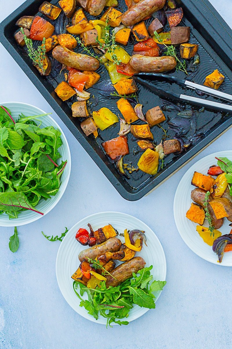 Overhead shot of Easy Sausage and Sweet Potato Traybake - half still in the tray, half on two plates with a side salad