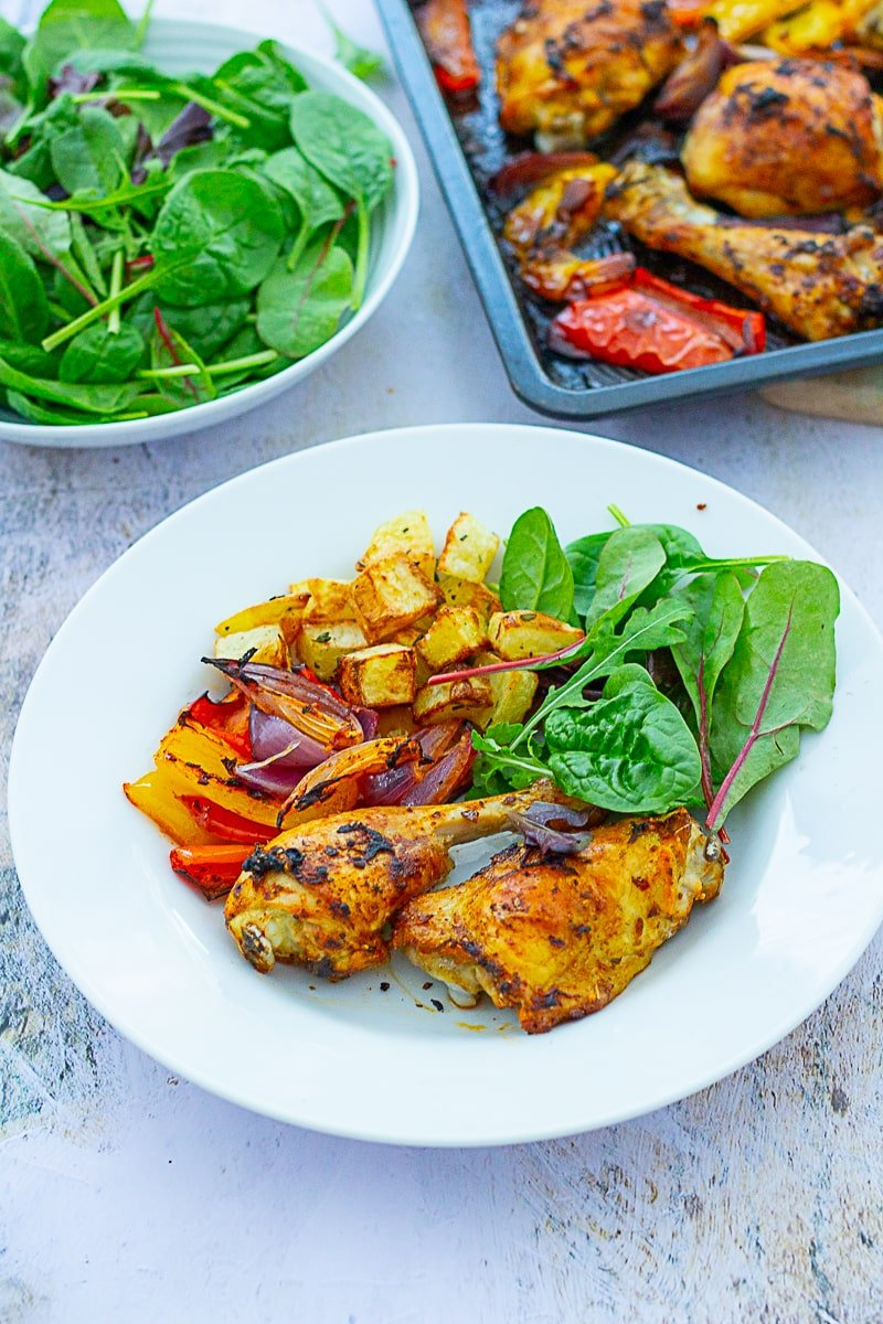 Nandos-inspired Peri Peri Chicken Traybake served on a plate with Parmentier Potatoes and green salad