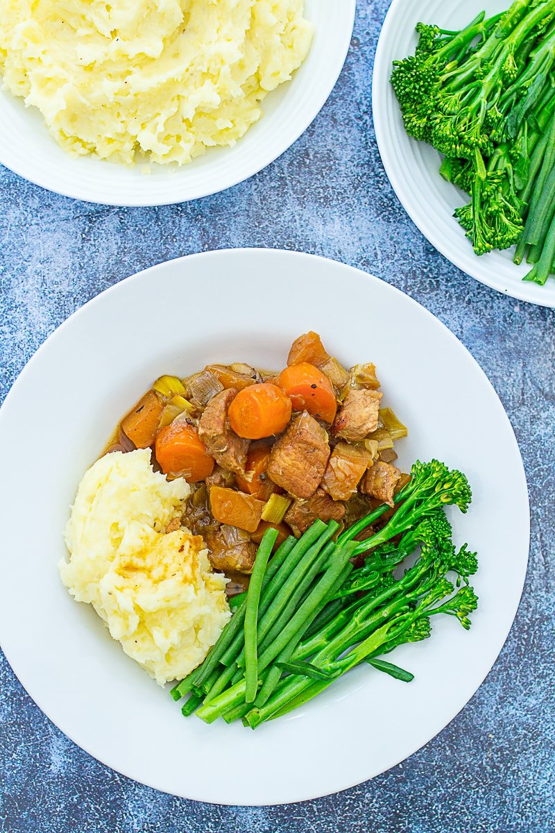 Overhead of Diced Pork and Apple Stew on a plate with mashed potatoes and green vegetables