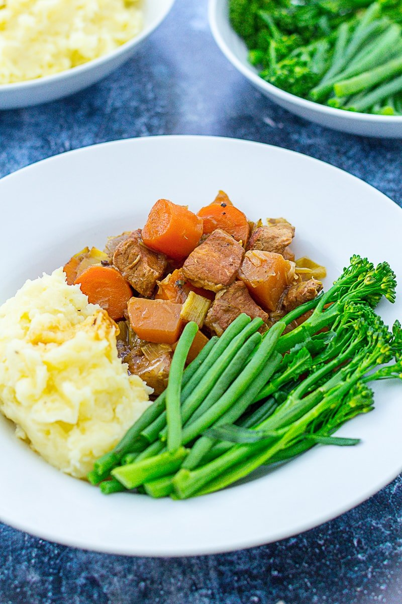 Diced Pork and Apple Stew on a plate with mashed potatoes and green vegetables