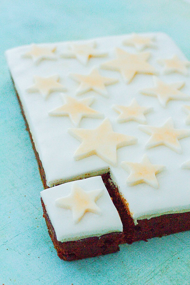Easy Christmas Cake Traybake with one slice cut and pulled away from the rest of the cake, slightly