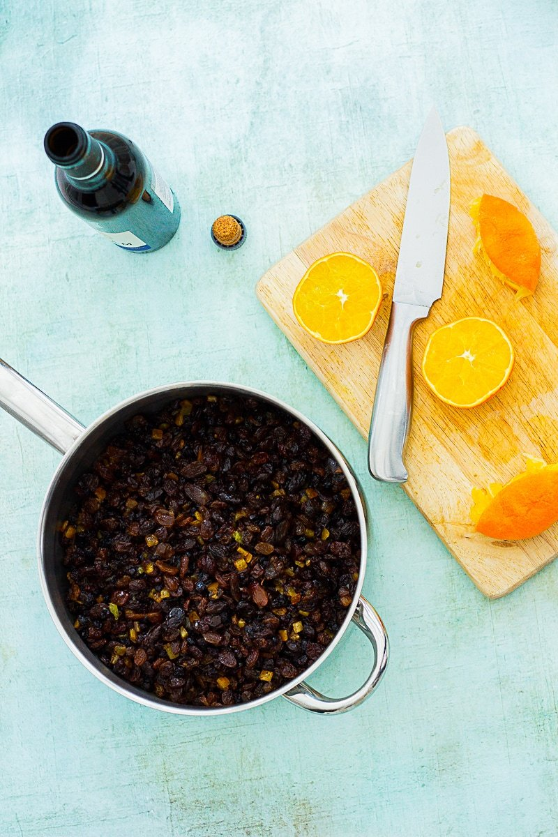 Mixed dried fruit in a saucepan, next to a chopping board with a knife and orange halves and a bottle of sherry