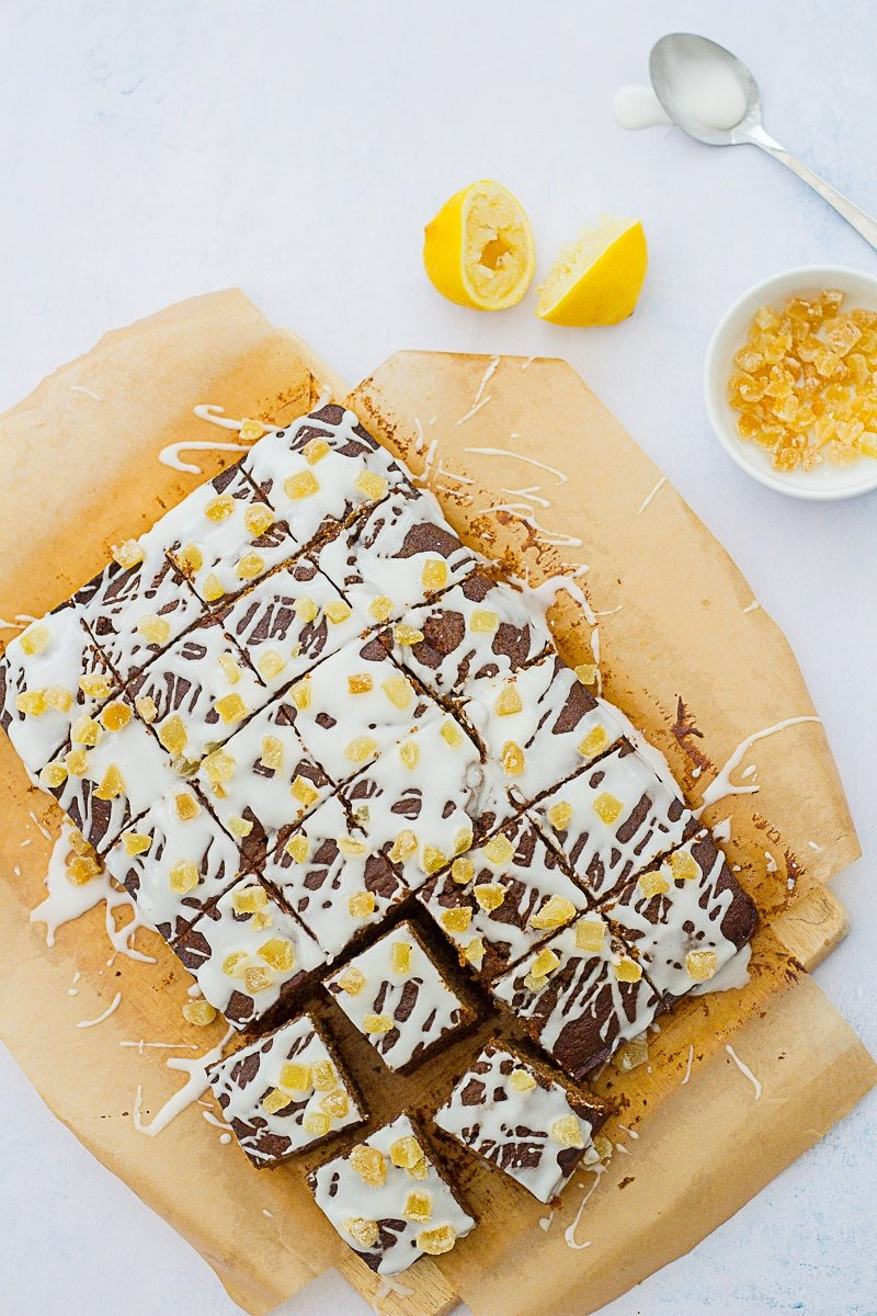 Easy Gingerbread Traybake Cake - overhead shot of this cake, cut into 24 squares, next to two squeezed out lemon halves, a tablespoon covered in icing and a small bowl of crystallised ginger cubes