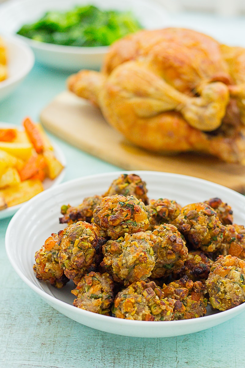 Easy Apricot and Pistachio Stuffing Balls in the front of the shot with roast chicken and vegetables behind