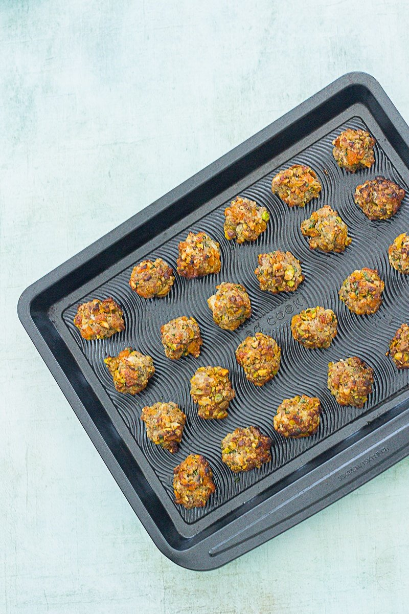 Easy Apricot and Pistachio Stuffing Balls on a baking tray having just come out of the oven