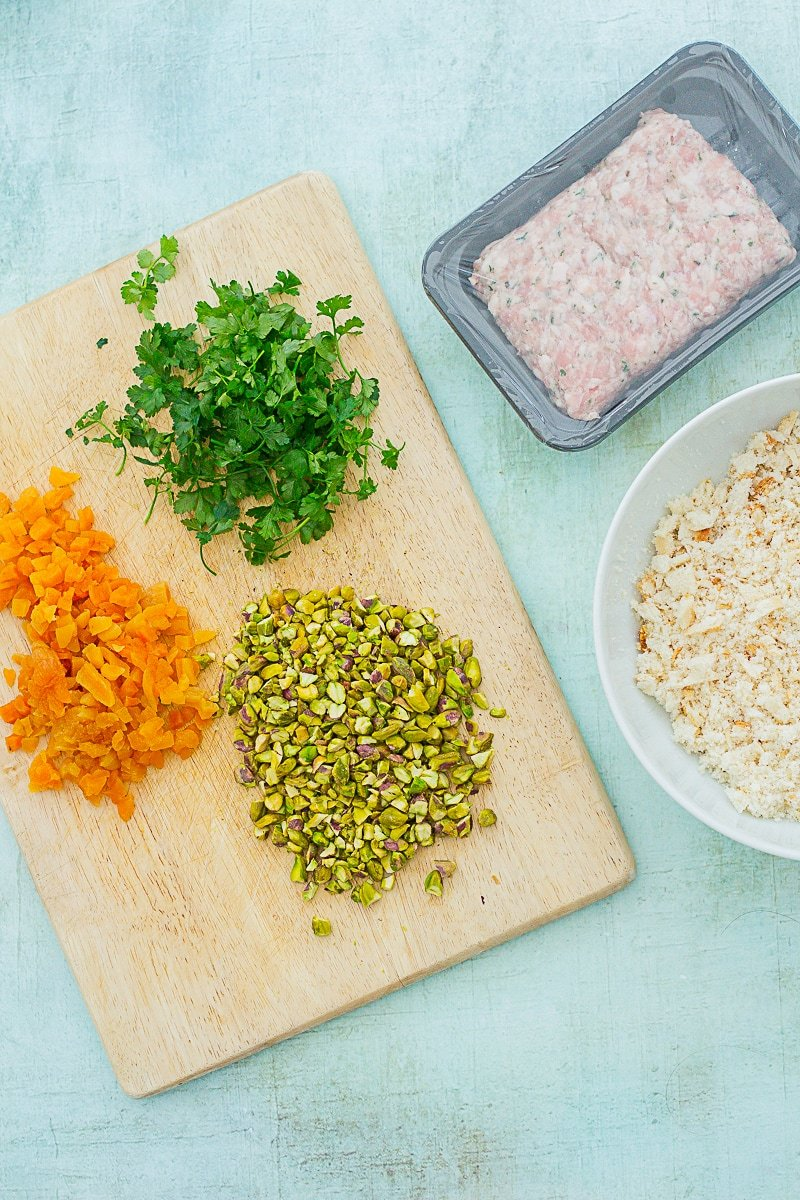 Chopped apricots, pistachios and parsley on a board next to breadcrumbs in a bowl and a pack of sausage meat