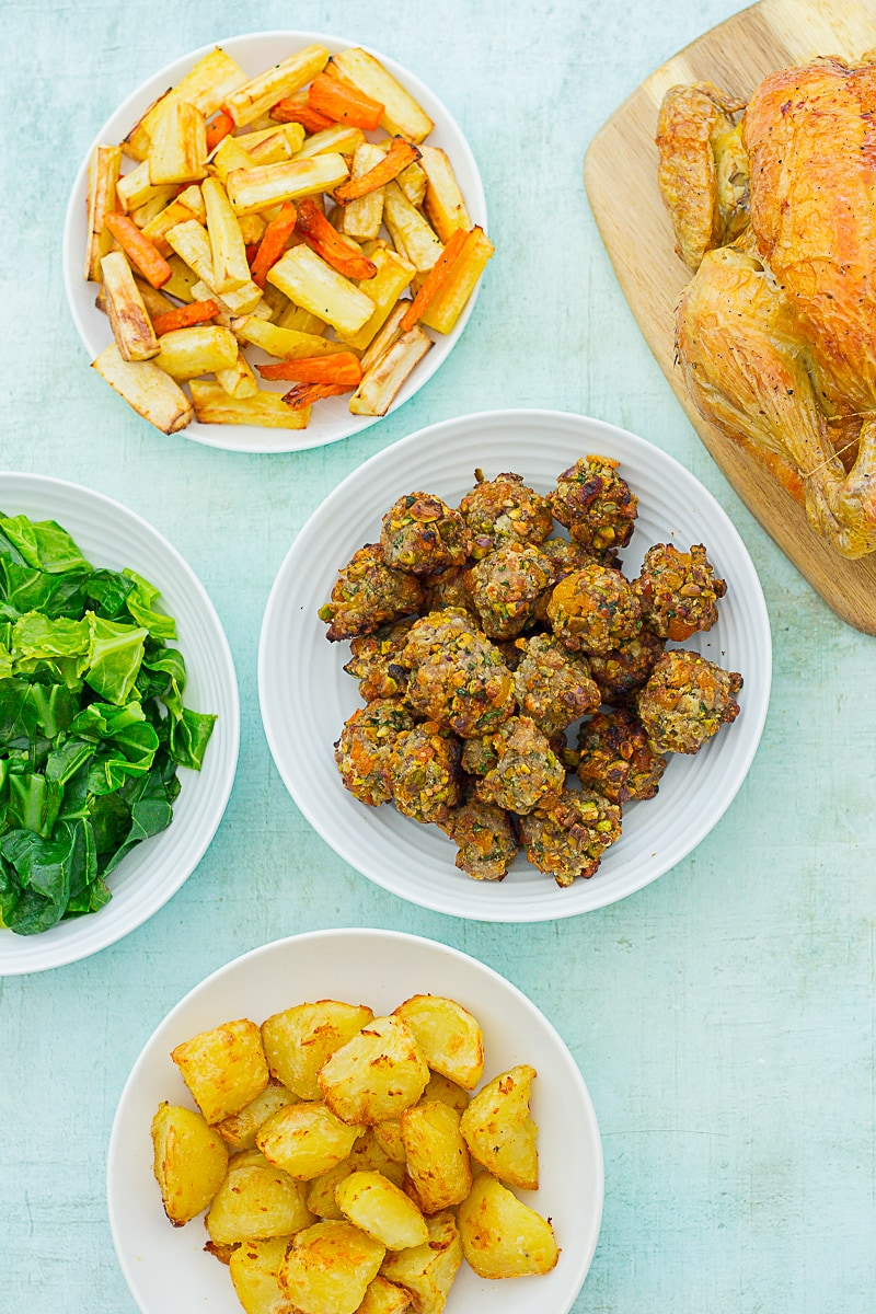 Overhead shot of Easy Apricot and Pistachio Stuffing Balls in a bowl surrounded by roast chicken, roast potatoes, roast parsnips and carrots and steamed greens