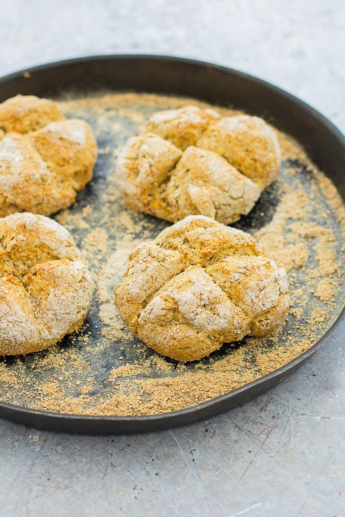 4 cooked soda bread rolls on a baking tray