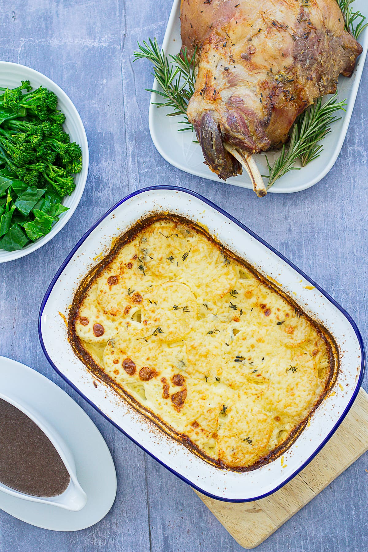 Overhead shot of Easy Dauphinoise Potatoes next to gravy, greens and roast lamb shoulder