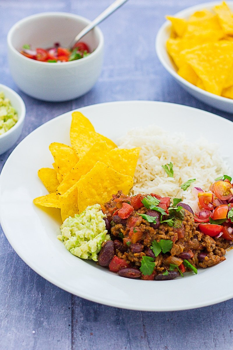 Easy Peasy Chilli Con Carne on a plate with guacamole, salsa and tortilla chips
