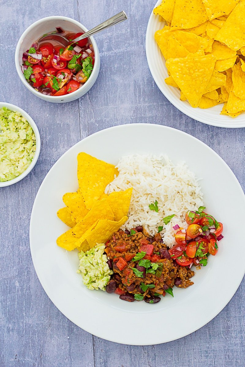Overhead shot of Easy Peasy Chilli Con Carne on a plate with guacamole, salsa and tortilla chips