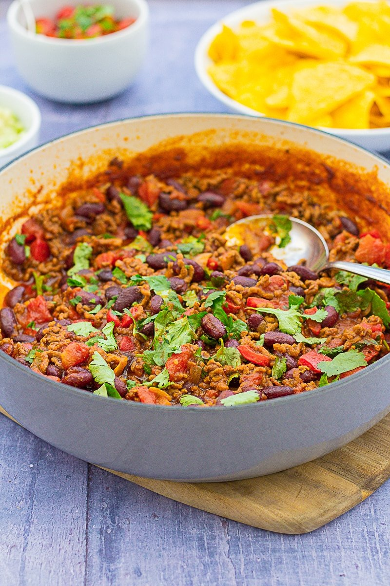 Easy Peasy Chilli Con Carne in a pan in front of guacamole, salsa and tortilla chips