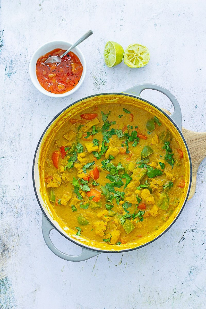 Overhead shot of Chicken, Red Lentil and Coconut Curry in the pan next to two lime halves and mango chutney