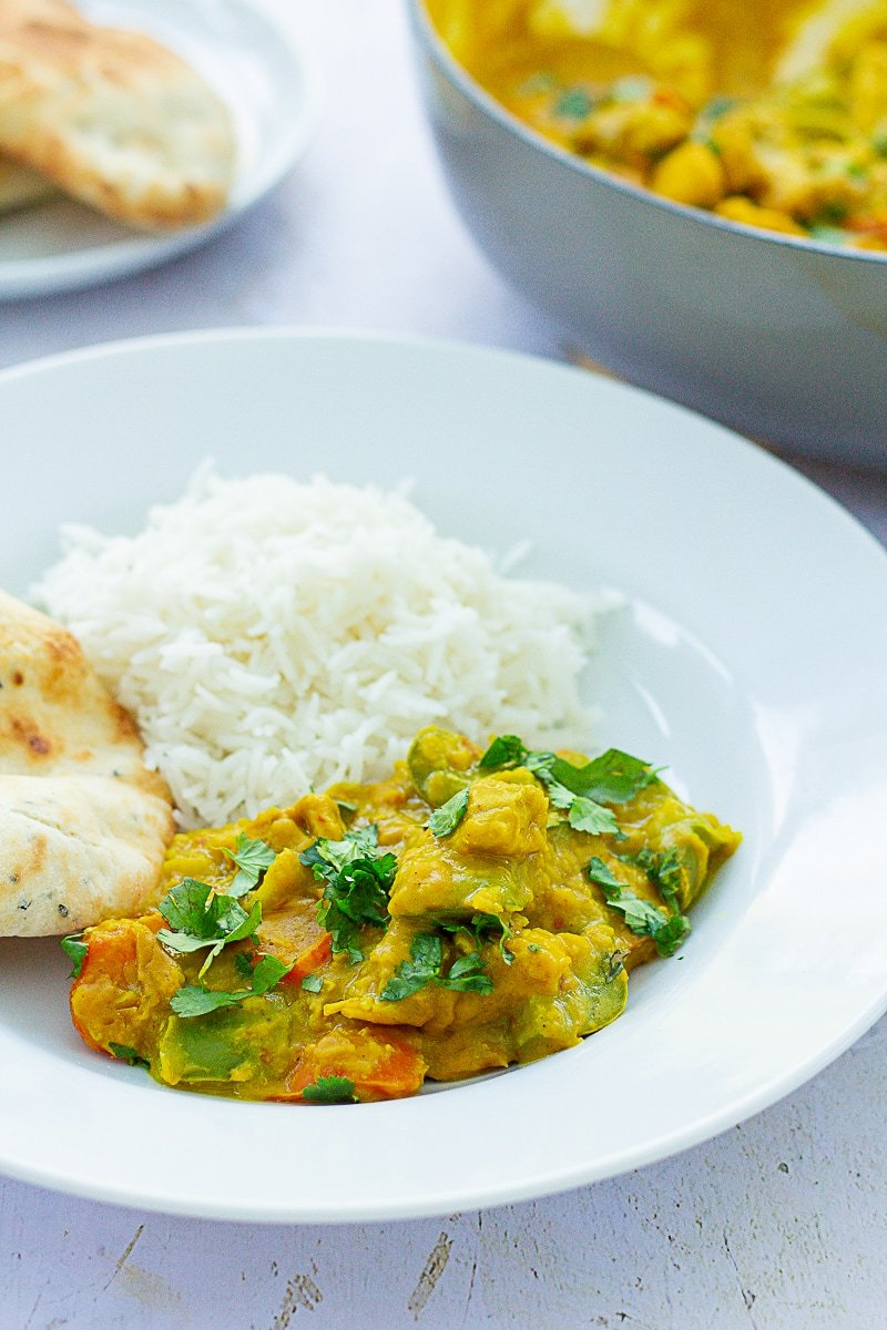 Chicken, Red Lentil and Coconut Curry on a plate with rice and a naan