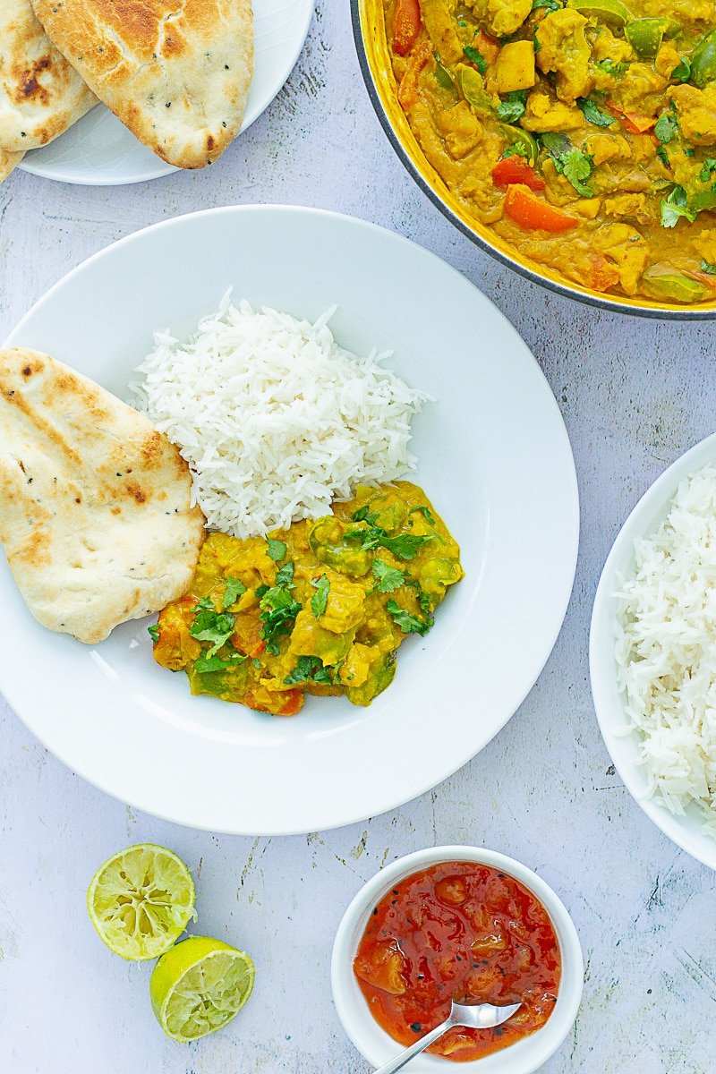 Overhead of Chicken, Red Lentil and Coconut Curry on a plate next to limes, mango chutney, rice and naans