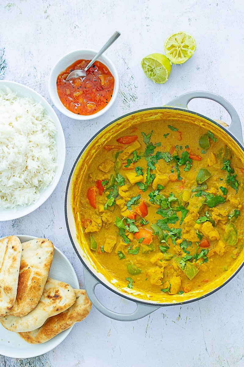 Overhead of Chicken, Red Lentil and Coconut Curry in the pan next to limes, mango chutney, rice and naans