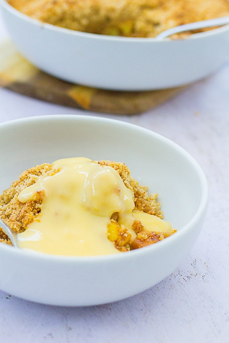 Closeup of Easy Peasy Apple Crumble covered in custard