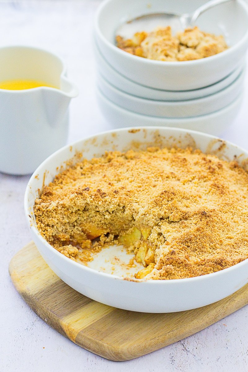 Easy Peasy Apple Crumble in forground, with custard and bowls in the background